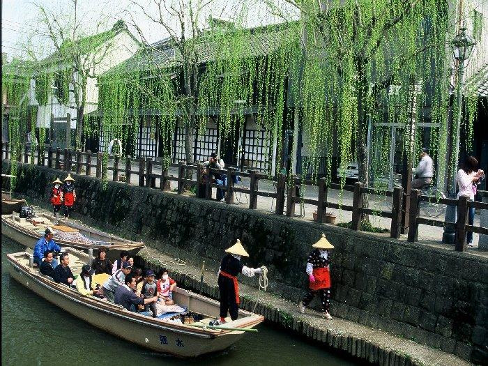 舟に乗りながら古くから栄えた水郷の町を眺める